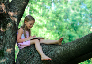 Little girl with a book on a tree branch