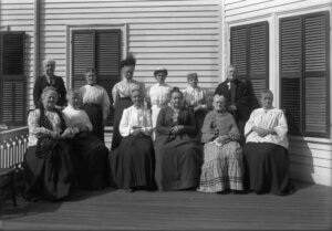Group of twelve Old Ladies' Home residents seated on a porch